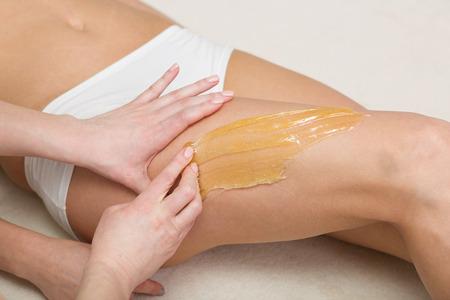 salon treatment: Beautiful woman having a sugaring depilation beauty treatment