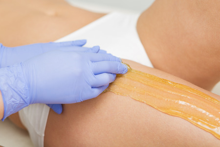 sugaring: Beautiful woman having a sugaring depilation beauty treatment