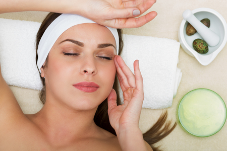 treatment: Beautiful woman having a facial massage beauty treatment Stock Photo
