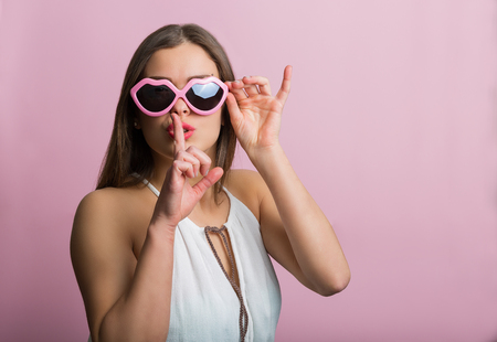 finger on lips: Pretty woman holding finger at lips
