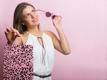 sexy young woman: Pretty woman with pink glasses and shopping bag Stock Photo