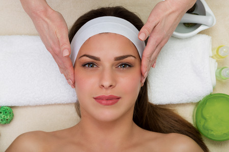 Beautiful woman having a facial massage beauty treatment Фото со стока