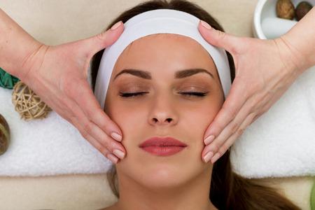 masaje facial: Mujer hermosa que tiene un tratamiento de belleza masaje facial