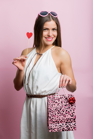 sexy kiss: Pretty woman with pink glasses and shopping bag Stock Photo