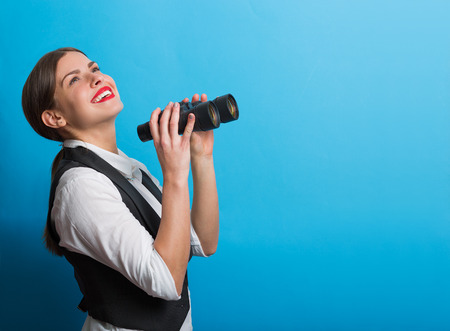 searching for: Pretty woman holding binoculars. Searching for new opportunities business concept