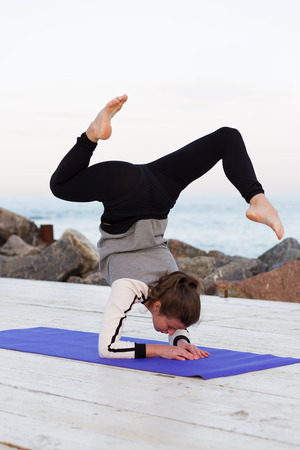 yoga outside: Sportive young woman practicing yoga outside by the sea Stock Photo