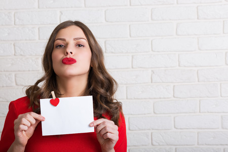 red lips: Beautiful woman in red dress holding a love letter Stock Photo