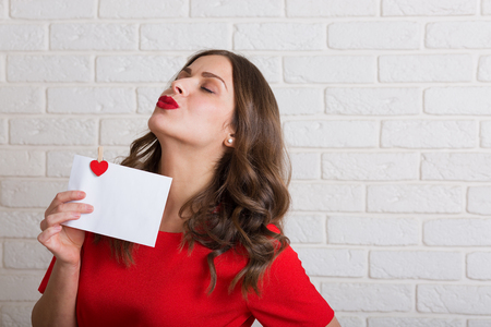 love letter: Beautiful woman in red dress holding a love letter Stock Photo