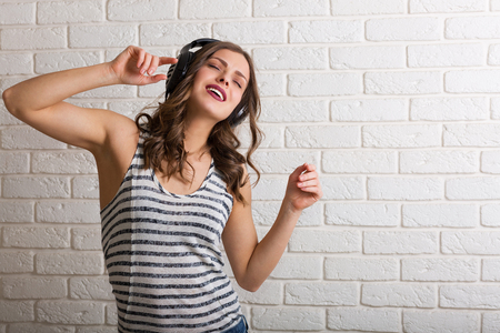 brick background: Pretty woman listening to music and dancing Stock Photo