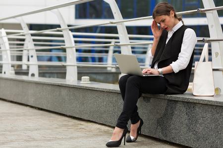 Femme d'affaires travaillant à l'extérieur en face du bâtiment du centre de businnes Banque d'images