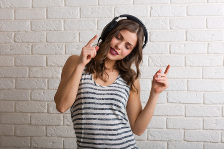 brown background: Pretty woman listening to music and dancing Stock Photo
