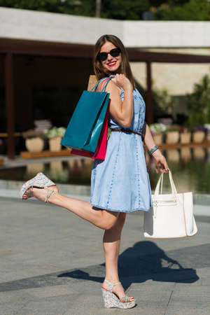 lady in red: Stylish woman with shopping bags in summer city Stock Photo