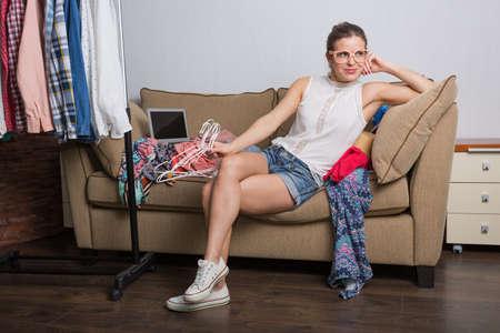 compras compulsivas: Shopaholic hipster girl at her home sorting her wardrobe Foto de archivo