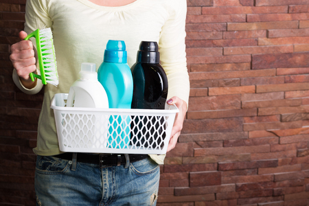 Woman holding basket with various detergent bottles