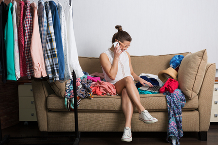 compras compulsivas: Mujer joven inconformista ordenar su armario Foto de archivo