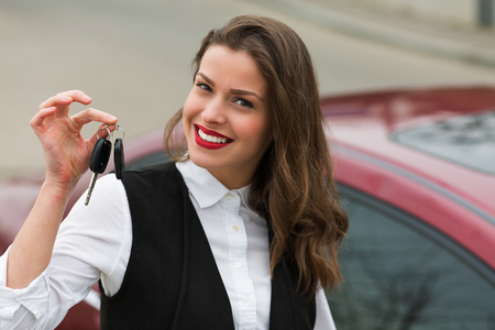 car dealers: Business woman with car keys standing near her car