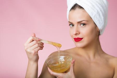 Mujer que sostiene el pelo de azúcar en la eliminación de la pasta Foto de archivo - 54016699