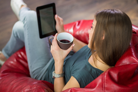 彼女の自宅で女性のデジタル読書本します。 写真素材 - 57976855