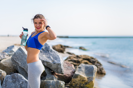 rehydration: Woman working out at the beach Stock Photo