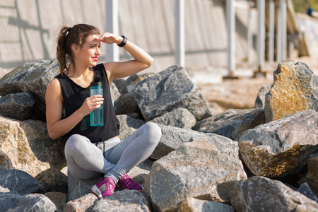 rehydration: Woman resting after training outside at the beach
