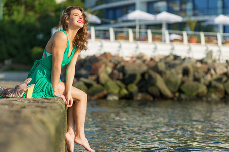 Beautiful woman in a green dress at the beach