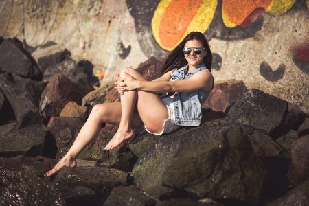 aviators: Beautiful young woman sitting alone at the summer beach