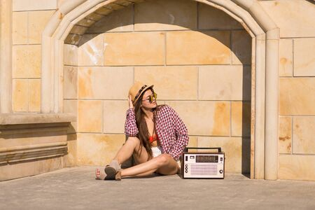 bandeau: Beautiful young boho woman with a retro stereo sitting on a street