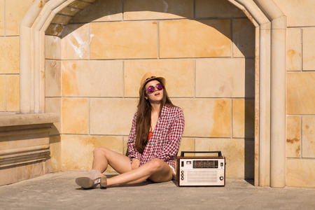 Beautiful young boho woman with a retro stereo sitting on a street