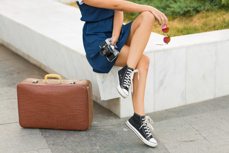 woman resting: Pretty woman with a retro suitcase in the summer city