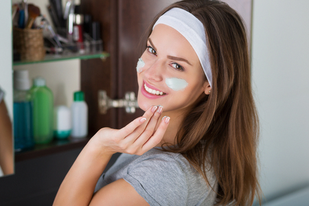 moisturizer: Woman applying moisturizer. Skin care treatment and beauty concept. Stock Photo