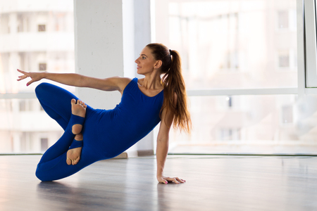 Young beautiful woman practicing yoga in a studio Stock Photo