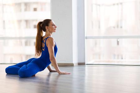 Young beautiful woman practicing yoga in a studio Stock Photo