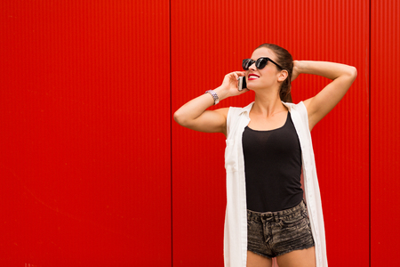 Stylish woman with a cell phone  standing agains red wall