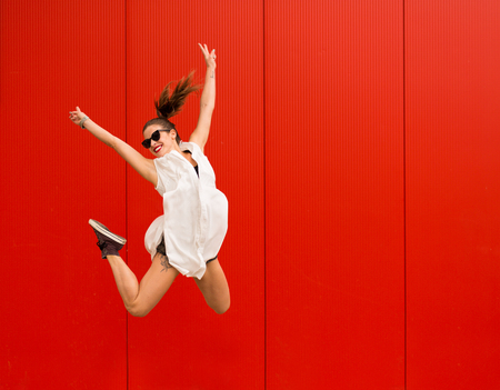 Stylish woman dancing and jumping on a street agains a red wall Stock Photo