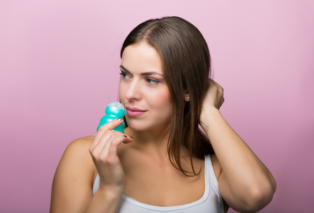 Woman holding a deodorant antiperspirant bottle Stock Photo