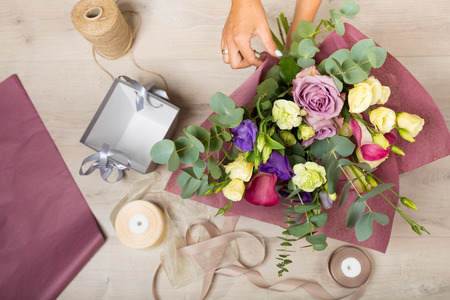 Flowers and floristic equipment arranged on a wooden background