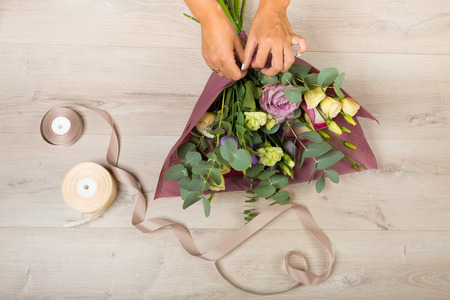 card making: Flowers and floristic equipment arranged on a wooden background