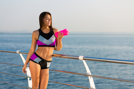 rehydration: Beautiful young woman working out at the seaside