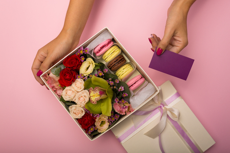 Flowers and macaroons in a hat-box over the pink background