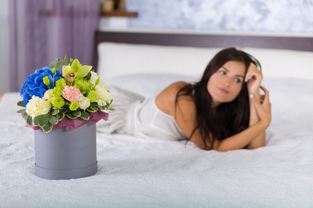 bed skirt: Woman holding a lovely hat box with flowers