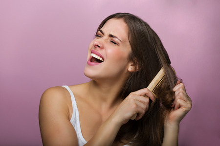 damaged: Woman brushing her hair with a wooden comb