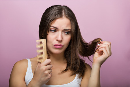 comb hair: Woman brushing her hair with a wooden comb