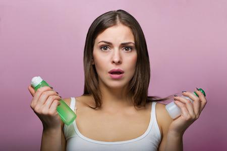 スキンケア製品のボトルを保持しているきれいな女性 写真素材 - 64013225