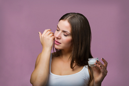 Woman with a bottle of a skin care product