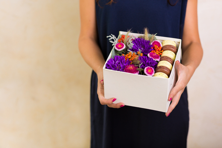 Woman holding a surprise box with flowers and macaroon cookies
