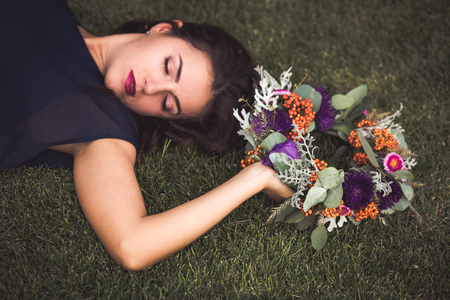 Beautiful woman with a flower crown laying on a grass