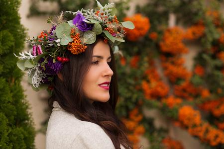 Pretty woman in a flower crown in an autumn garden