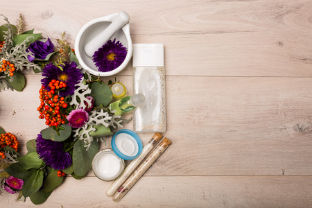 skincare products: Seasonal skincare products with flower wreath on a wooden background