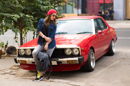 Pretty stylish woman standing by the red retro car