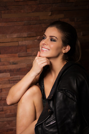 updo: Stylish woman in a leather jacket near a brick wall
